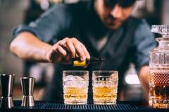 Barista che aggiunge gli ingredienti del cocktail sui cocktail del whiskey alla barra Fotografia Stock