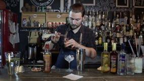 Barista che lavora in ingredienti di miscelazione del pub in agitatore per la fabbricazione dei cocktail video d archivio