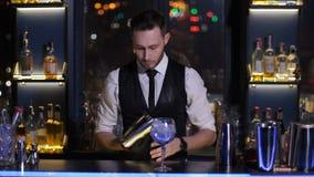 Barista che mette ghiaccio in cocktail vetrario alla barra archivi video
