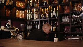 Barista che mette ghiaccio e che versa whiskey in vetro archivi video