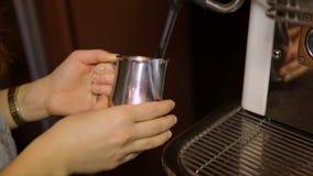 Barista che monta latte in un barattolo su una macchina professionale del caffè video d archivio