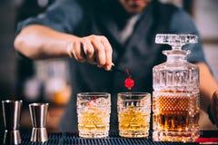 barista che prepara e che allinea i vetri di cristallo del whiskey per le bevande alcoliche Fotografia Stock