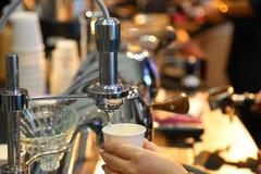 Barista che prepara il nero lungo o il caffè di Americano con la macchina di caffè espresso nella mattina con luce calda fotografia stock libera da diritti