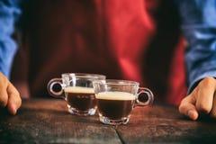 Barista che tiene due tazze del caffè espresso Immagine Stock