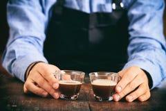 Barista che tiene due tazze del caffè espresso Fotografie Stock