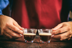 Barista che tiene due tazze del caffè espresso Fotografia Stock
