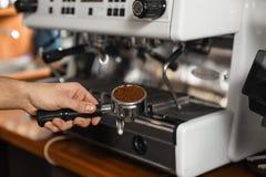 Barista che tiene portafilter con caffè macinato vicino alla macchina nella barra, primo piano fotografie stock
