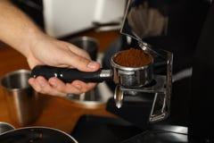 Barista che versa caffè macinato dalla macchina per la frantumazione nel portafilter immagine stock libera da diritti