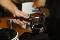 Barista che versa caffè macinato dalla macchina per la frantumazione nel portafilter fotografia stock