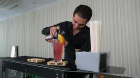 Barista che versa il cocktail della bevanda mista dall'agitatore nel vetro al rallentatore stock footage