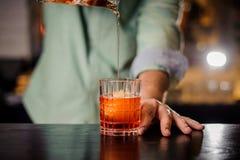Barista che versa il cocktail nel vetro con iceball Immagine Stock