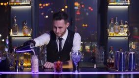 Barista che versa la bevanda pronta del cocktail in vetro video d archivio