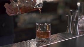 Barista che versa un cocktail di rinfresco dell'alcool o del whiskey in un vetro con ghiaccio Fine in su Movimento lento video d archivio