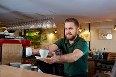 Barista with coffee cup in hand behind bar. royalty free stock photography