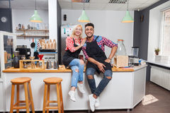 Barista coffee shop owner couple happy smile sitting on bar counter Royalty Free Stock Photography