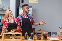 Barista coffee shop owner couple happy smile welcome at bar counter mix race man woman Stock Image