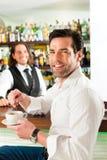 Barista con el cliente en su café o coffeeshop foto de archivo