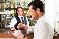 Barista con il cliente nel suo caffè o coffeeshop Fotografie Stock