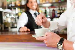 Barista con il cliente nel suo caffè o coffeeshop Immagini Stock