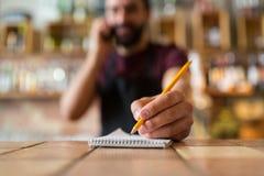 Barista con il taccuino e la matita alla barra Immagine Stock