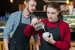 Barista course learning profession young man study. Barista courses. learning new profession and education concept. young men studying how to make latte or Royalty Free Stock Photos