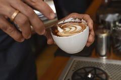 Barista, das auslaufende Milch der Kaffeesahne im Becher verziert mit Schaum zubereitet lizenzfreies stockbild