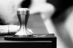 Barista, das in einer Kaffeestube, Abschluss oben von barista arbeitet, drückt gemahlenen Kaffee unter Verwendung des Besetzers,  lizenzfreies stockfoto