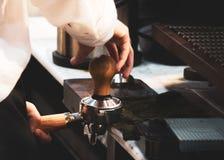 Barista, das in einer Kaffeestube, Abschluss oben von barista arbeitet, dr?ckt gemahlenen Kaffee unter Verwendung des Besetzers,  lizenzfreie stockfotografie