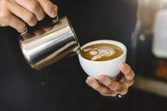 Barista, das Kaffee Lattekunst macht lizenzfreies stockbild