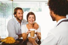 Barista, das zwei glückliche Kunden dient Lizenzfreies Stockfoto