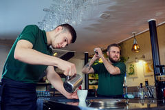 Barista de dos camareros que trabaja detrás de la barra en el lugar de trabajo Imágenes de archivo libres de regalías