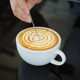 Barista decorate top surface of latte art coffee. In white cup on black background Royalty Free Stock Photography