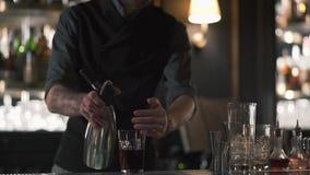 Barista dei pantaloni a vita bassa che per mezzo dell'agitatore e facendo un cocktail dell'alcool nella bella barra moderna Movim stock footage