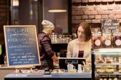 Barista della donna alla cassa della caffetteria o del caffè Immagini Stock