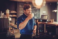 Barista die een nieuw type van koffie in zijn koffiewinkel proeven stock foto's