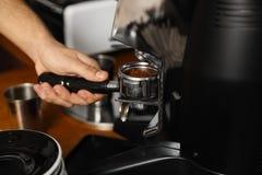 Barista die gemalen koffie van malende machine gieten in portafilter stock afbeelding