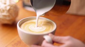 Barista draws milk over a coffee - making latte art for cappuccino. Barista making of cafe latte art, heart shape stock video