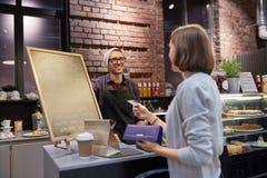 Barista e donna che pagano con la carta di credito al caffè Fotografie Stock Libere da Diritti