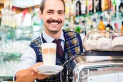 Barista en barra de café ofrece macchiato del latte en vidrio Foto de archivo libre de regalías