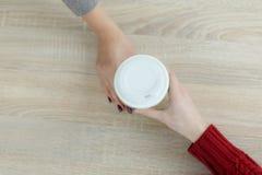 Barista en delantal está dando el café caliente en taza de papel para llevar verde al cliente El café se lleva en la tienda del c fotos de archivo