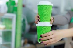 Barista en delantal se est? sosteniendo en caf? caliente de las manos en taza de papel para llevar verde El caf? se lleva en la t foto de archivo