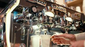 Barista está haciendo el café para llevar en una taza no reutilizable usando la máquina en el café almacen de metraje de vídeo