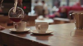 Barista está vertiendo el café de un fabricante de café del vacío en dos tazas blancas colocadas en la tabla de roble suave, en u almacen de metraje de vídeo
