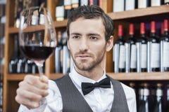 Barista Examining Red Wine in vetro al negozio Immagini Stock