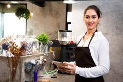 Barista fêmea caucasiano bonito usando a tabuleta e sorrindo dentro da cafetaria Imagens de Stock