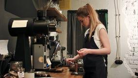 Barista fêmea consideravelmente novo que pesa grãos de café em uma escala antes de fabricar cerveja uma xícara de café Fotos de Stock