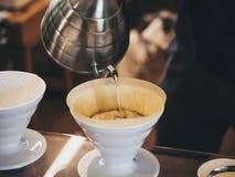 Barista för handdroppandekaffe hällande vatten på kaffejordning arkivfoton