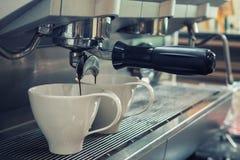 Barista förbereder espresso i hans coffee shop med maskinen royaltyfria foton