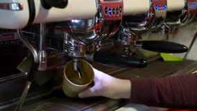 Barista faz o caf? O empregado de bar novo fabrica cerveja o caf? na m?quina do caf? Movimento lento Fim do copo de papel acima video estoque