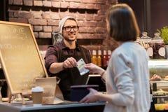 Barista felice e donna che pagano soldi al caffè Immagine Stock Libera da Diritti
